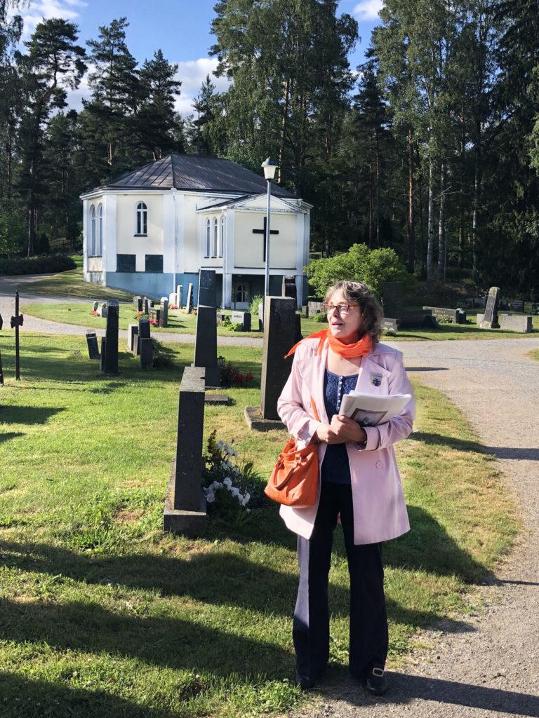 Opas Leena Lehtinen Asikkalan hautausmaalla. Taustalla siunauskappeli